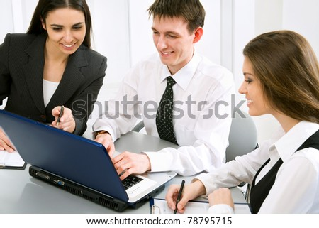 Three business people at the office with a laptop - stock photo