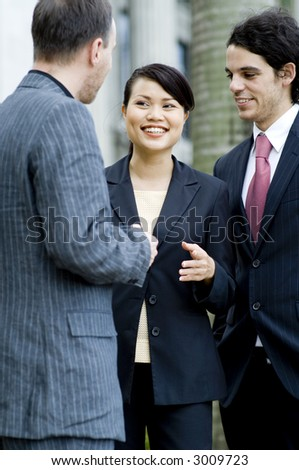 Three business people chatting together outside