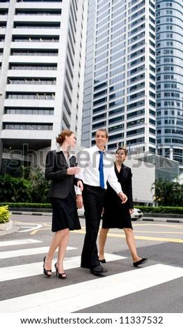 Three business people crossing road on zebra crossing - stock photo