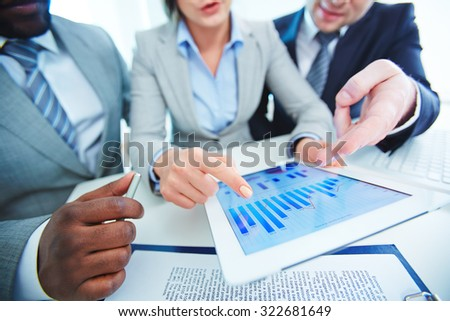 Three business people discussing data in touchpad