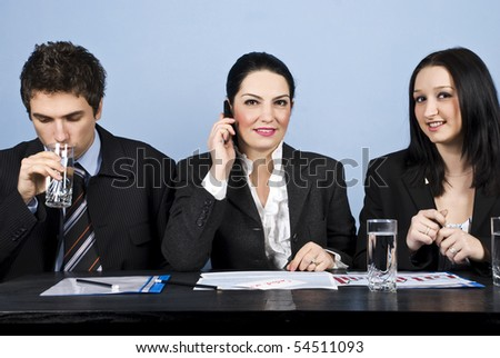 Three business people having a meeting or a conference and all sitting in a line at table,businessman drinking water,a businesswoman speaking at phone mobile and the other woman smiling at you - stock photo