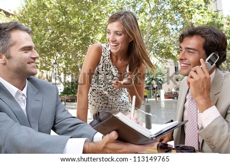 Three business people having a meeting while sitting at a coffee shop terrace outdoors.