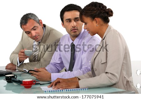 Three business people having coffee during meeting - stock photo