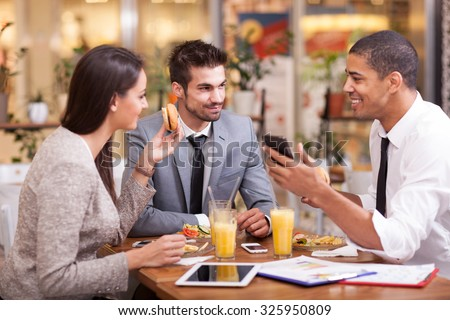 Three Business people Having Meeting In Outdoor Restaurant - stock photo
