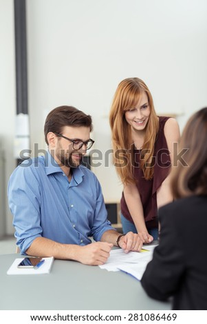 Three business people in a meeting in the office with focus to an attractive redhead woman standing leaning on the table alongside a male colleague - stock photo