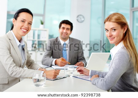 Three business people looking at camera in office - stock photo