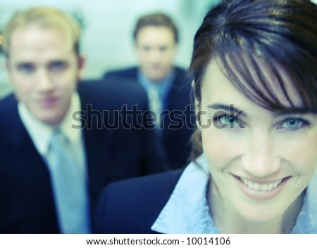 three business people looking at camera staggered on stairs - stock photo