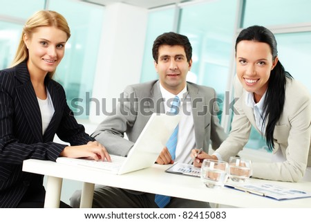 Three business people looking at camera while at workplace - stock photo