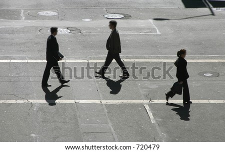 Three business people pass in the cross walk. - stock photo