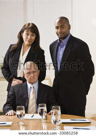 Three business people posing for photo. African American male and woman standing, male senior sitting in front of them. Vertical. - stock photo