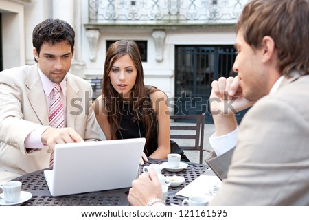 Three business people sharing a table at a coffee shop terrace, having a meeting and talking while using technology in the financial city district. - stock photo