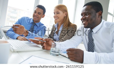 Three business people sharing ideas in office - stock photo