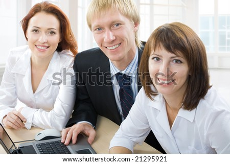 Three business people sit at the table - stock photo