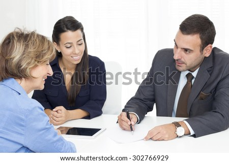 Three business people  sitting around a desk and working  in the office . - stock photo