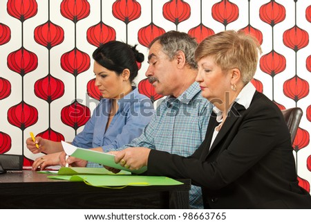 Three business people sitting at meeting table and working togheter in office - stock photo