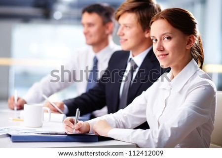 Three business people sitting at seminar with smiling woman at foreground - stock photo