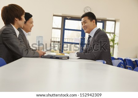 Three business people sitting in company cafeteria - stock photo