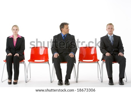 Three Business People Sitting On Red Plastic Seats - stock photo