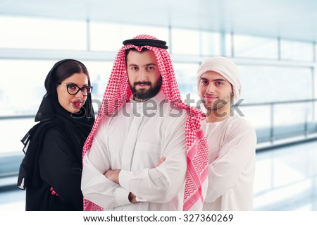 Three business people standing in a modern office interior, ethnic business people, business team, success concept - stock photo