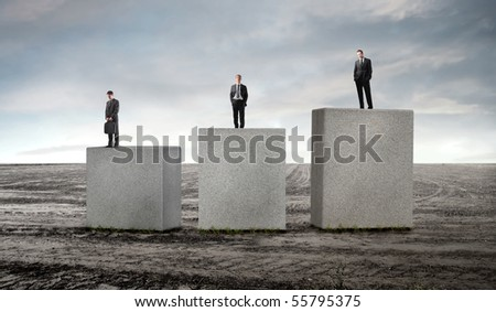 Three business people standing on cubes of different height - stock photo