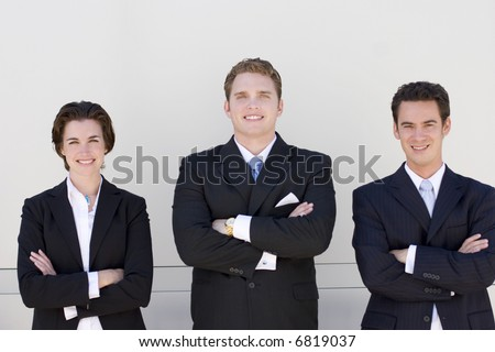 three business people standing side by side looking at camera smiling with white background