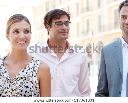 Three business people standing together next to a classic office building in the city on a sunny day, smiling. - stock photo