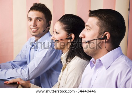 Three business people support operators working in office,focus on last man that looking and smiling you