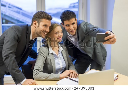 Three business people taking a Selfie in the office - stock photo