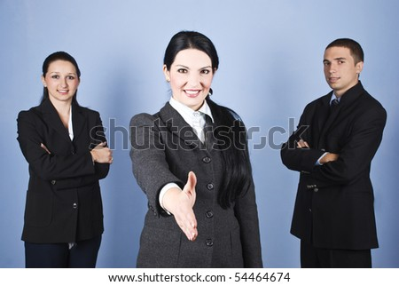 Three business people team standing and smiling for you with a businesswoman in front of image giving hand shake