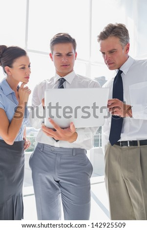 Three business people using a laptop while working in a bright office