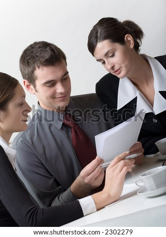 Three business person looking at paper sheet and discussing something, smiling