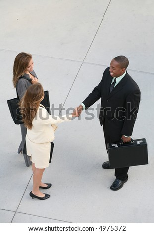 Three business professionals, man and women, shaking hands - stock photo