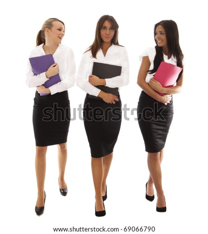 three business woman walking together all carrying document folders - stock photo