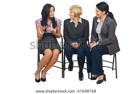Three business women having a happy discussion at conference and sitting on chairs isolated on white background - stock photo