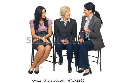 Three business women having conversation at conference and sitting together on cgairs isolated on white background