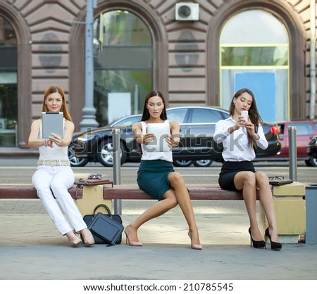 Three business women sitting on a bench in the summer city - stock photo