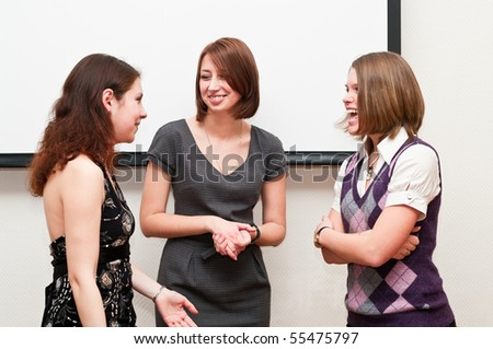 Three business women talking together in office room - stock photo