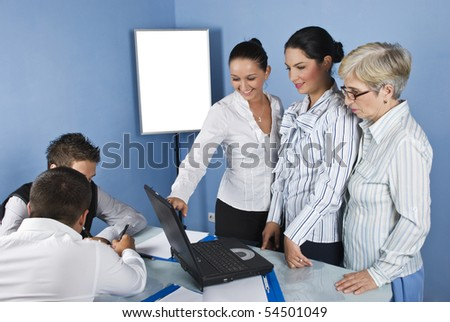 Three business women using a laptop and one of them pointing to screen and the other business men sitting at table in office meeting