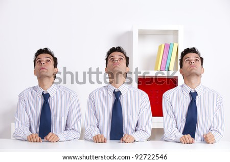 Three businessman at the office desk looking up - stock photo