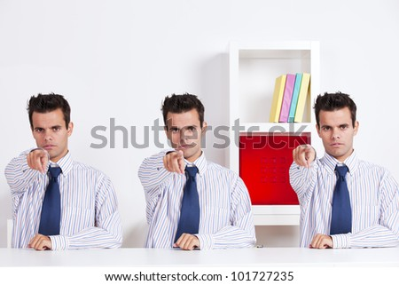 Three businessman behind the office desk pointing to you - stock photo