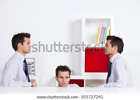 Three businessman looking at each other behind the office desk - stock photo