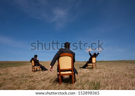 three businessman sitting in a chair in outdoor looking to the field - stock photo