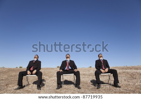 three businessman sitting in a chair in outdoor looking up