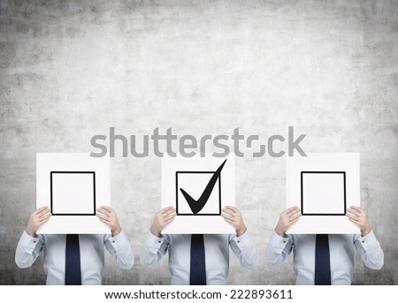 Three businessmen are holding a check boxes, a concept of decision making process. - stock photo