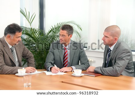 Three businessmen during a meeting - stock photo