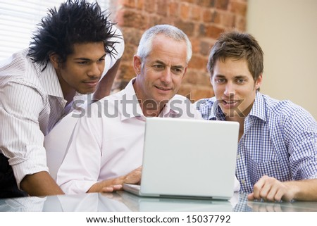 Three businessmen in office looking at laptop smiling