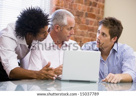 Three businessmen in office with laptop talking - stock photo