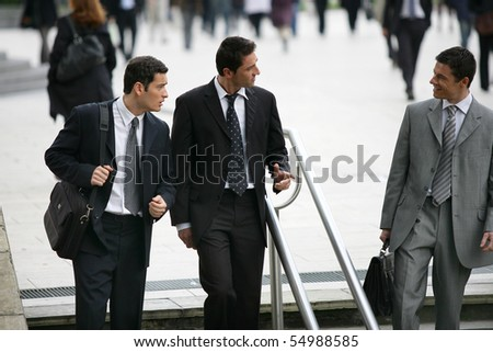 Three businessmen in suit coming down stairs - stock photo