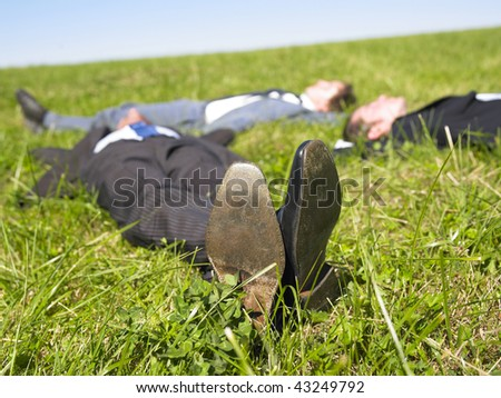 Three businessmen lying in the grass. Horizontal. - stock photo