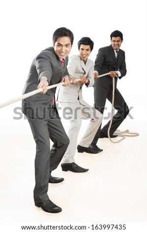 Three Businessmen playing tug-of-war - stock photo
